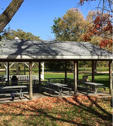 Wooden shelter in a park during fall with six picnic tables