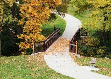 Raccoon River Trail during the fall with orange and yellow leaves on the trail's bridge