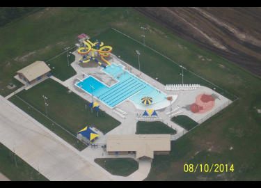 Bird's-eye view of Adel Aquatic Center's pool, waterslides, and lounge area