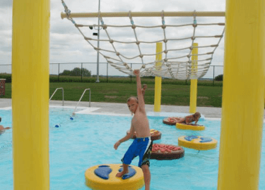 Little boy swinging on ropes and standing on lily pads in pool