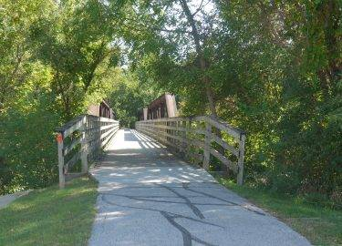 Entrance to the paved Raccoon River Valley Trail that leads through a forest