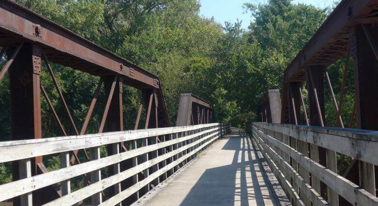 Sunny paved trail with wood rails and a bridge going over water