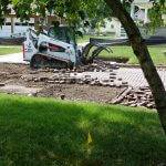White and orange Bobcat track loader removing red brick off of street