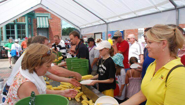 A large group of people in line waiting for corn cobs to be put on their plates