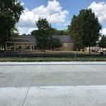 Concrete road construction in front of gazebo and Raccoon Valley Bank building